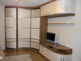 Гнутый шкаф-купе с зоной под телевизор из МДФ с красивым бронзовым пластиком